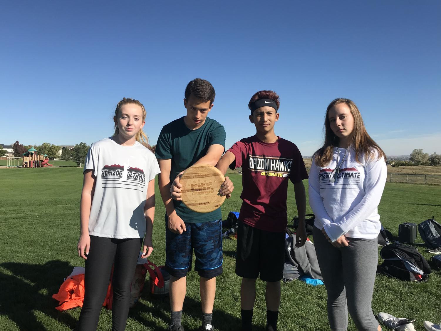 Madison Endicott (10) - Junior Captain, Samuel Ruiz-Harding (10) - Junior Captain, Ethan Tran (10) - Head Captain, and Emily Dhainin (12) - Head Captain pose with their Spirit Award which they won during the 2017-2018 season