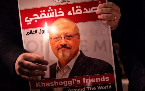 A demonstrator holds a poster picturing Saudi journalist Jamal Khashoggi and a lightened candle during a gathering outside the Saudi Arabia consulate in Istanbul, on October 25, 2018. - Jamal Khashoggi, a Washington Post contributor, was killed on October 2, 2018 after a visit to the Saudi consulate in Istanbul to obtain paperwork before marrying his Turkish fiancee.